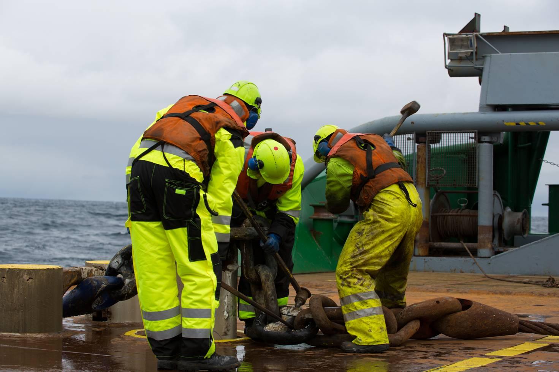 Tre mannskap med ryggen til jobber ombord
